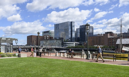 grassy area at Atlantic Wharf Waterfront with people walking around or sitting on benches overlooking the river